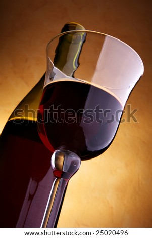 Glass and bottle of red wine over dark background