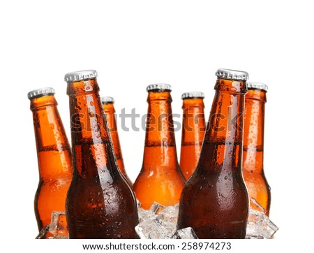Glass bottles of beer in ice cubes isolated on white