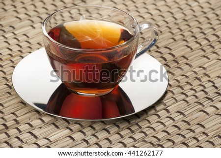 Glass cup of black tea with metal saucer on a matting woven cloth
