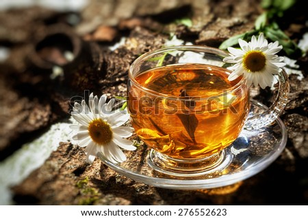 Glass cup with tea and daisy flower on old wooden table.
