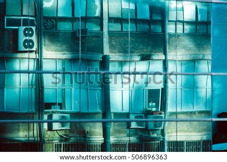 Glass curtain wall office building exterior glass, distorting and reflecting an old building that itself is illuminated by the sun reflecting on the same curtain wall from a different angle.