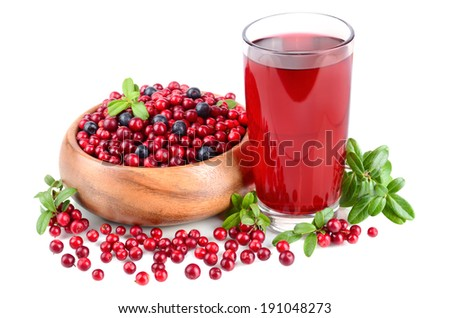 Glass fill of cowberry juice and whortleberrys in a round wooden bowl on white background