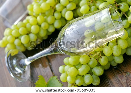 Glass goblet and a bunch of grapes.