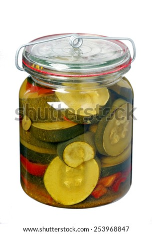 Glass jar with pickled zucchini isolated on white background