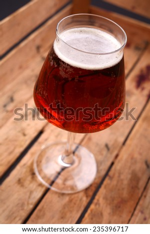 Glass of amber beer standing in an old dirty wooden crate