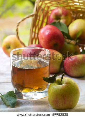 Glass of apple juice with basket of apple in background