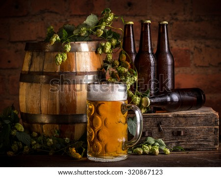 Glass of beer, old oak barrel and hops on wooden table.