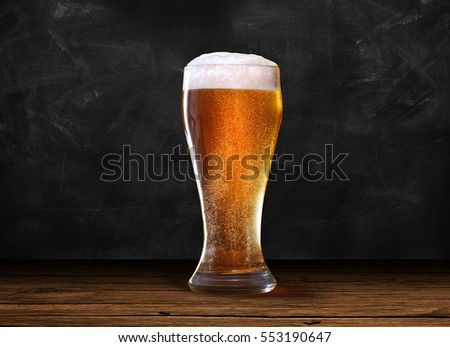 Glass of beer on the center of rustic table and dark chalk background