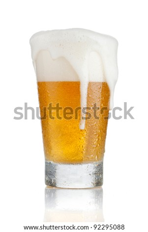 Glass of beer with foam coming out