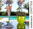 Glass of champagne on the glass table in outdoor resort bar - stock photo