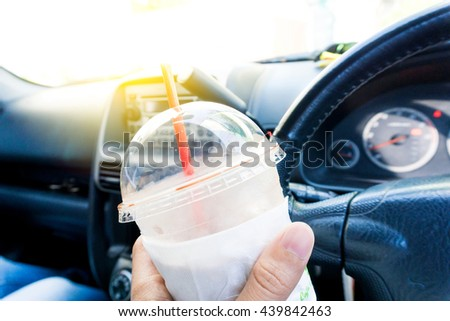 Glass of chocolate ice milk in car, Ready for cafein drive