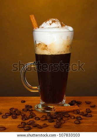 glass of coffee cocktail with coffee beans on brown background