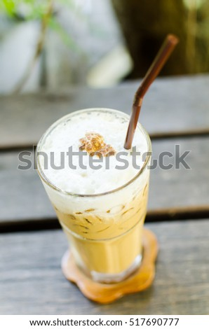 Glass of cold coffee on wooden table