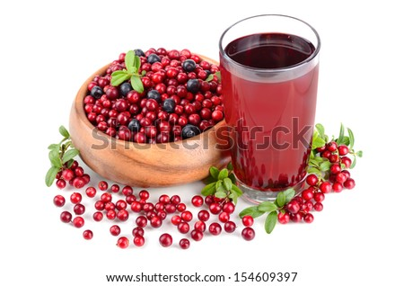 Glass of cowberry juice and whortleberrys in a round wooden bowl on white background