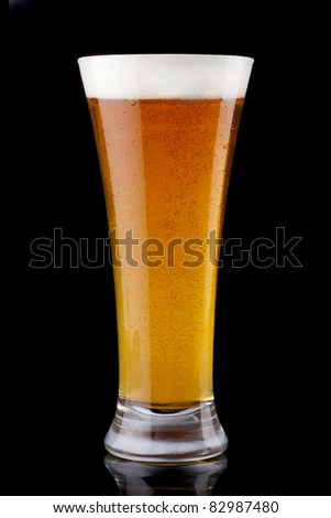 Glass of fresh beer on a black background