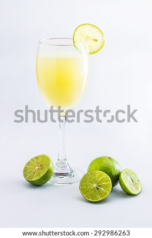 Glass of lime juice on white background