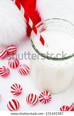 Glass of milk in a jar with a red straw.