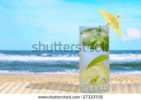 Glass of Mojito cocktail with umbrella at the beach