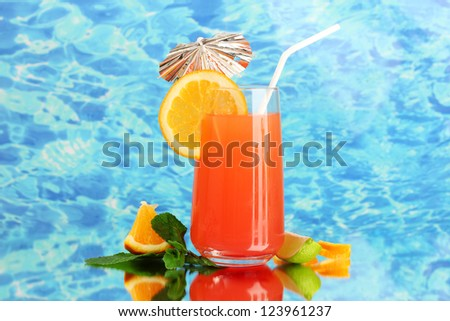 Glass of orange cocktail on blue background