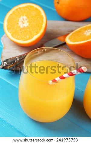 Glass of orange juice with straws and slices on cutting board with knife on color wooden background