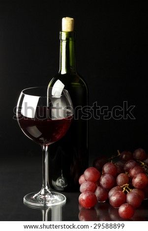 Glass of red wine, bottle and bunch of grape on black background.