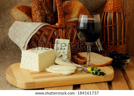 Glass of red wine, homemade cheese, cheese and a basket of bread