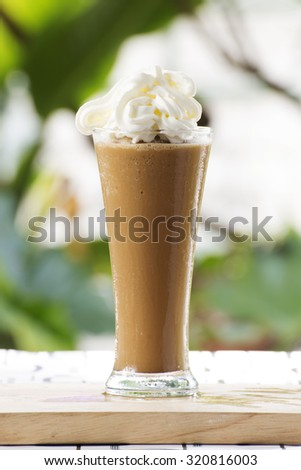 Glass of Thai Coffee smoothie topping with whip cream