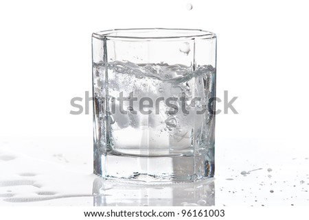 Glass of water and ice with splash on a white background