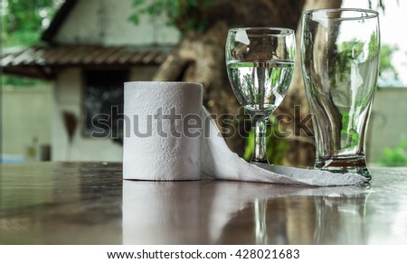 Glass of water and tissue paper is placed on a wooden table
