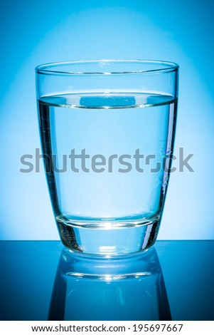 Glass of water isolated on blue background.