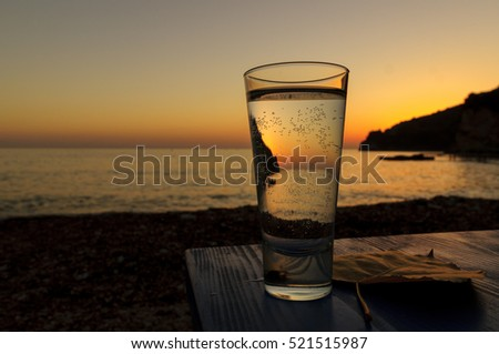 Glass of water on a beach in a colorful sunset