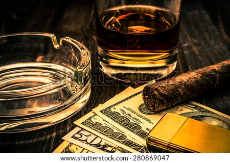 Glass of whiskey and a money with cuban cigar and golden lighter on a wooden table. Close up view, focus on the cuban cigar, image vignetting and the orange-blue toning