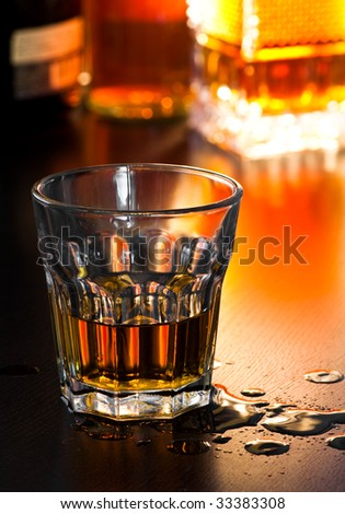Glass of whiskey on table with drops, shallow DOF