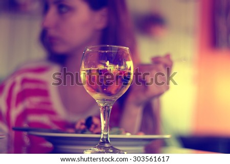 glass of white wine in a restaurant on a background of a person