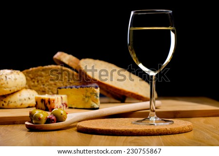 Glass of wine and cheese with bread on a background