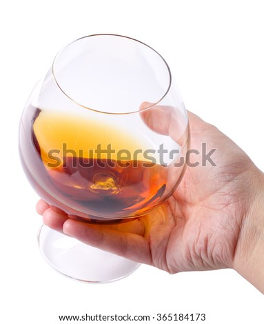Glass with cognac in a hand on white background isolated