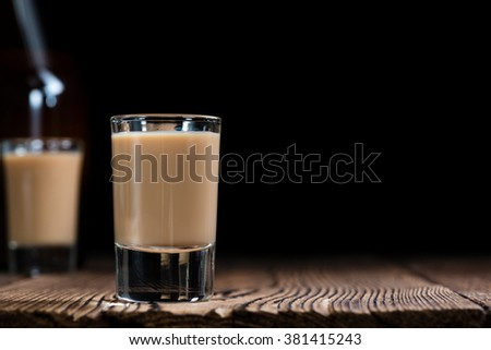 Glass with original Irish Cream Liqueuron wooden background