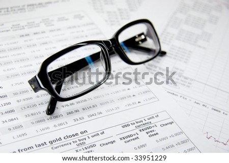 Glasses and financial documents close up