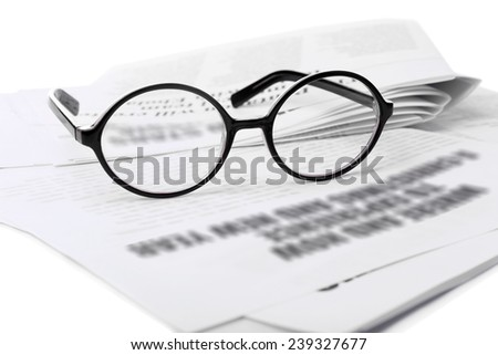 Glasses and newspapers, close-up