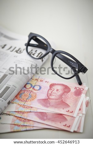 Glasses, newspaper and Chinese RMB bills