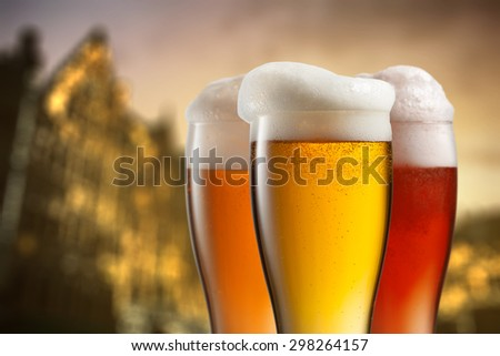 Glasses of beer against blurred european city with beautiful lights on background at evening