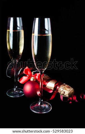 Glasses of champagne with botlle on black background