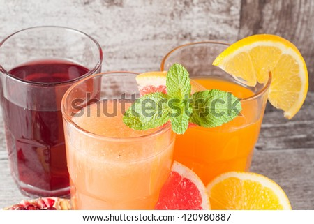 Glasses of pomegranate, grapefruit, orange juice on wooden background. Refreshments and summer drinks.