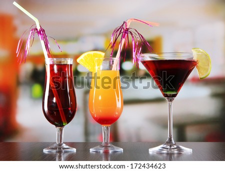 Glasses of tasty cocktails on bright background