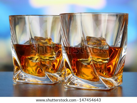 Glasses of whiskey, on bright background
