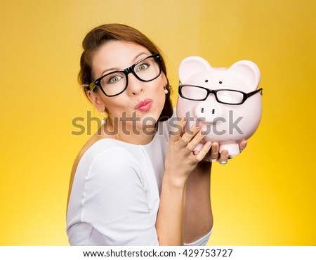 Glasses sale concept. Happy woman kissing piggy bank wearing eyewear glasses. Female model isolated on yellow background.