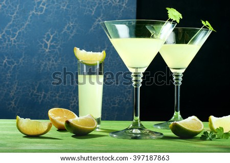 Glasses with lemon liqueur on green wooden board beside slices of lemon and lime. Alcoholic drink.