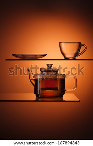 glassy tapot with tea and empty teacup