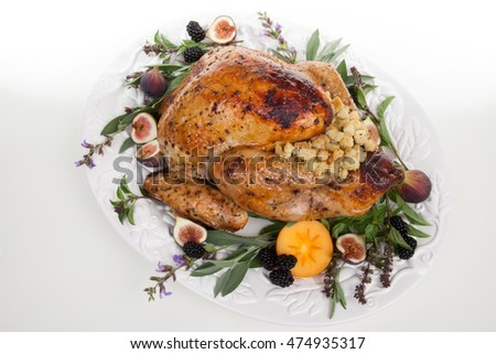 Glazed roasted turkey on serving tray over white background. Garnished with figs, blackberry, persimmon, sage, and basil.