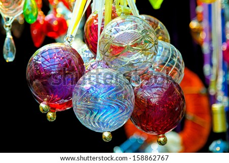 Glossy glass balls hanging on decorative ribbon as Christmas ornaments